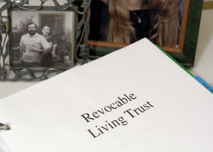 Revocable Living Trust documents with pictures of loved ones in the background.  main focus is on the documents.  Model release included for people in the pictures.