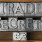 trade secrets phrase with dollar sign made from metallic letterpress type on wooden tray