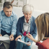 Mature Couple Meeting with Financial Advisor, selective focus to senior man and mature woman listening to financial advisor. She is pointing with pencil to some contract details.