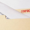 A legal confidentiality and non-disclosure agreement in a manila folder marked Confidential.