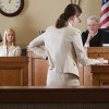 A lawyer questioning a witness in front of the judge in a courtroom.