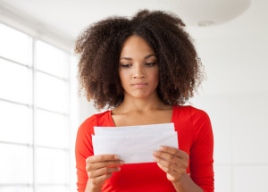 Woman looking at letter with concerned expression.